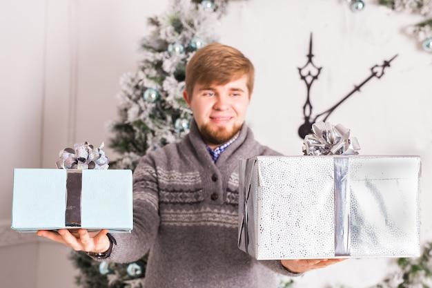 Święta i specjalne okazje. człowiek daje złote pudełko z czerwoną wstążką na białym tle. facet chowa się za plecami. niespodzianka. strzał studio.