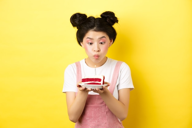 Święta i uroczystości. głupiutka azjatka z glamour makijaż, życzenia i dmuchająca świeca na tort urodzinowy, stojąca na żółto.