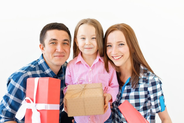 Święta i uroczystości koncepcja - szczęśliwa rodzina z prezentami świątecznymi na białym tle.