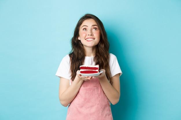 Święta i uroczystości. marzycielska urodzinowa dziewczyna życząca i patrząca w górę z nadzieją, trzymająca tort urodzinowy i uśmiechnięta, stojąca na niebieskim tle.