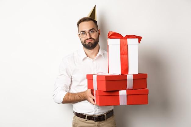 Święta i uroczystości. niezadowolony facet trzymający prezenty urodzinowe i wyglądający na rozczarowanego, który nie lubi prezentów, stoi