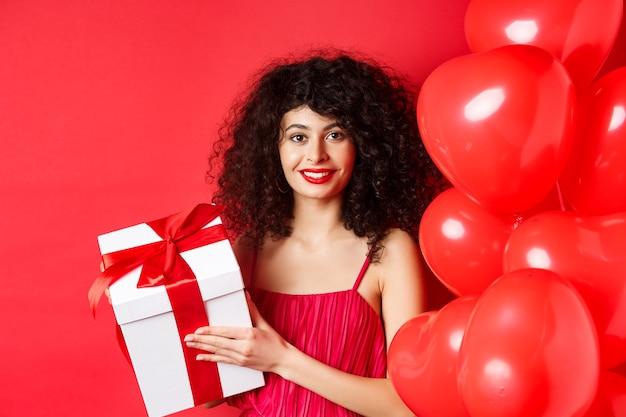 Święta i uroczystości. piękna kobieta z kręconymi włosami, stojąca w pobliżu balonów serca, trzymając pudełko i uśmiechnięty szczęśliwy, białe tło.