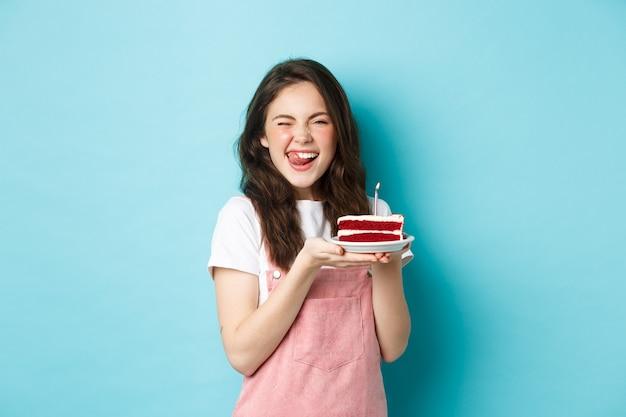 Święta i uroczystości. podekscytowana kobieta życząc na tort urodzinowy, mrugając i uśmiechając się zadowolony do kamery, świętuje, stojąc na niebieskim tle.