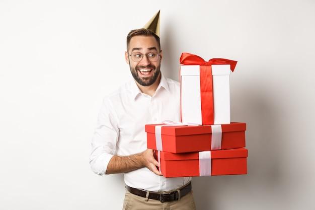 Święta i uroczystości. podekscytowany mężczyzna o przyjęcie urodzinowe i odbieranie prezentów, patrząc szczęśliwy, stojący na białym tle.