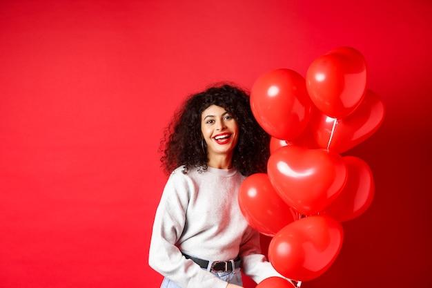 Święta i uroczystości. szczęśliwa kobieta pozuje z balonów na czerwonej ścianie.