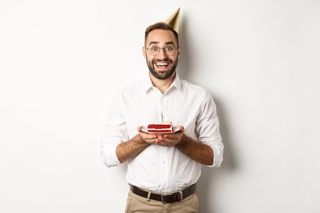 Święta i uroczystości. szczęśliwy człowiek mający przyjęcie urodzinowe, życząc na tort urodzinowy i uśmiechnięty, stojąc na białym tle.