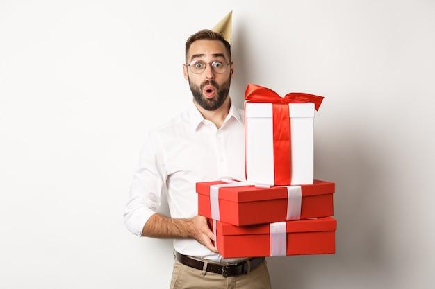 Święta i uroczystości. szczęśliwy człowiek otrzymujący prezenty na urodziny, trzymając prezenty i patrząc podekscytowany, stojący