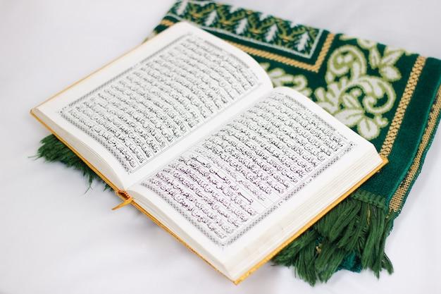 Święta księga al koran i dywanik modlitewny na białym tle