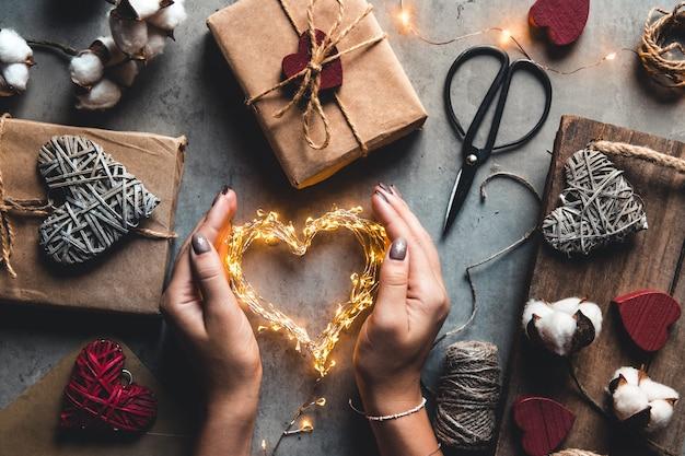Święta, ludzie i koncepcja uroczystości - zbliżenie kobiety dekorującej prezenty walentynkowe