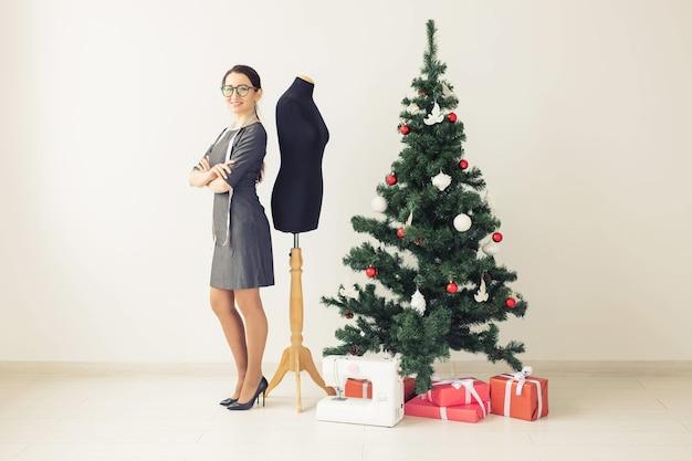 Święta, projektowanie odzieży i koncepcja prezentów - projektantka odzieży damskiej w pobliżu choinki, boże narodzenie w studiu krawieckim.