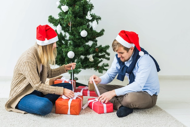 Święta, rodzina i świąteczna koncepcja - para z prezentami świątecznymi w domu.