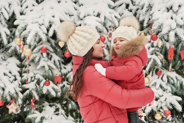 Święta rodzina w winter park. szczęśliwa rodzina matka i córka dziecko zabawy, grając w zimie chodzić na zewnątrz. rodzinna zabawa na świeżym powietrzu na boże narodzenie. zimowa odzież dla niemowląt i małych dzieci.