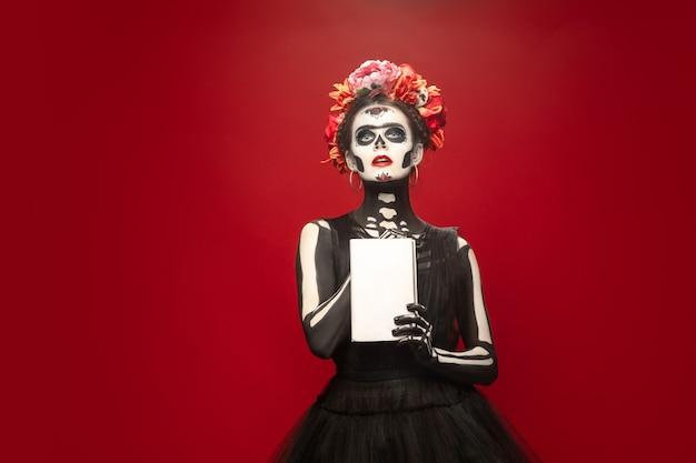 Święta śmierć lub cukrowa czaszka z jasnym makijażem na czerwono