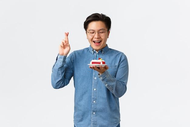 Święta świętowania i koncepcja stylu życia z nadzieją uśmiechnięty azjatycki facet z szelkami krzyżującymi palce dobre ...