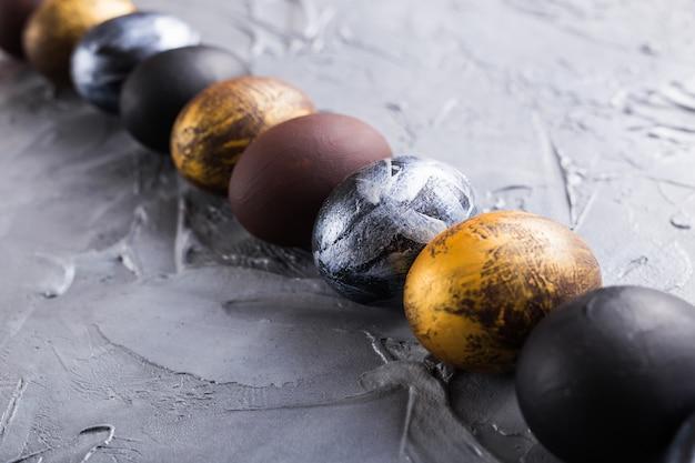 Święta, tradycje i koncepcja wielkanocna - ciemne stylowe pisanki na szarym tle.