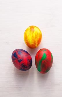 Święta, tradycje i koncepcja wielkanocna - wielobarwne ozdobne kolorowe jajka na białym tle z miejsca na kopię. widok z góry.