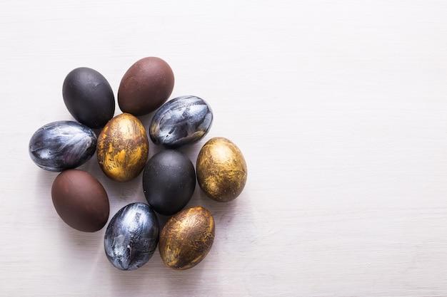 Święta, tradycje i wielkanocny pojęcie - ciemni stylowi easter jajka na białym drewnianym tle z copyspace.