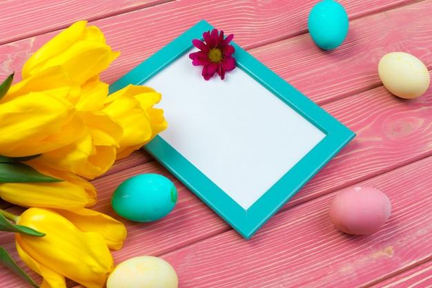 Święta wielkanocne . drewniana rama z easter jajkami i tulipanami na kolorowym