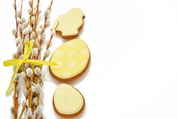 Święta wielkanocne. gałęzie wierzby cipki żółta wstążka i wielkanocne zające pierniki, kurczaki i jajka na białym tle