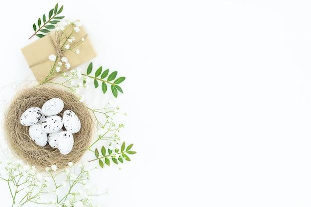 Święta wielkanocne jasne tło z białymi cętkowanymi jajkami w ptasim gnieździe, ekologiczne pudełko, małe białe kwiaty, zielone liście
