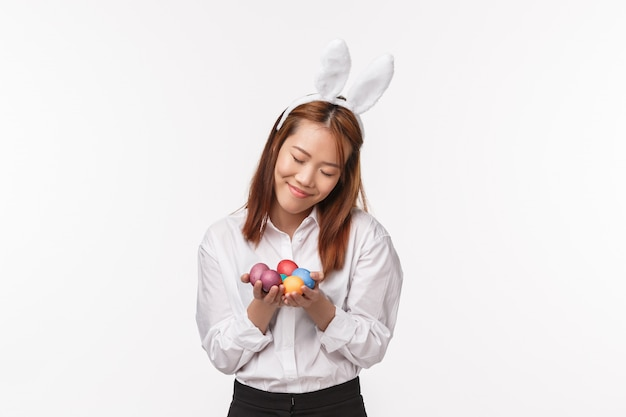 Święta wielkanocne, koncepcja uroczystości. portret uroczej i głupiej młodej nieśmiałej azjatyckiej dziewczyny w uszach królika, trzymającej pomalowane jajka i uśmiechającej się rumieńca skromnego