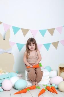 Święta wielkanocne! piękna mała dziewczynka na białej ścianie z marchewką, kolorowymi jajkami, koszem i zając. rodzinne wakacje, tradycje. żniwa, mały rolnik. rolnictwo. dekoracje wielkanocne, dekoracje wiosenne