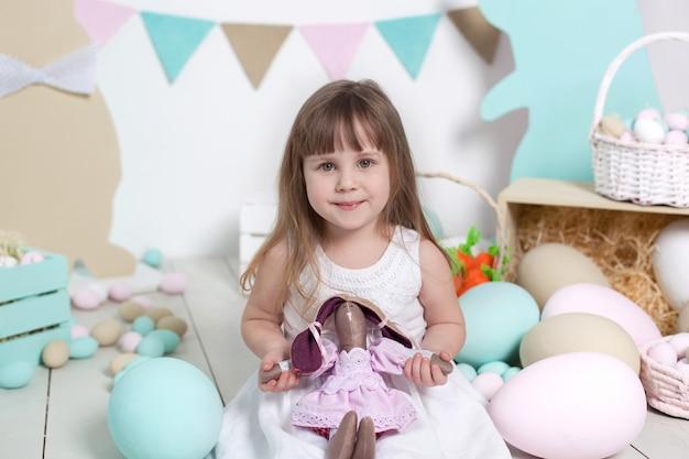 Święta wielkanocne! piękna mała dziewczynka w białej sukni przytula zabawkę zając. dziecko otrzymuje prezent i cieszy się z wakacji. wiele różnych pisanek, kolorowe wnętrze wielkanocne. zajączek wielkanocny. wiosenny wystrój