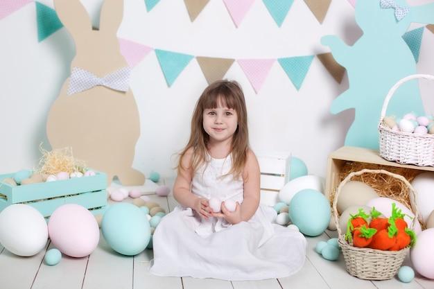 Święta wielkanocne. piękna mała dziewczynka w białej sukni trzyma wielkanocnych jajka. wielobarwne duże jajka w koszyku i wielkanocne króliczki. żniwa, mały rolnik. wielkanocna dekoracja, wiosenny wystrój. rodzinne wakacje.