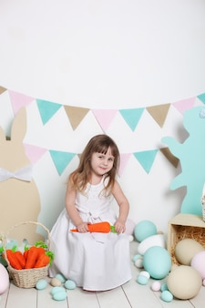 Święta wielkanocne! piękna mała dziewczynka w białej sukni z koszem z pisankami i wielkanocnymi króliczkami. wielkanocna dekoracja wnętrz, wiosenny wystrój. rodzinne wakacje. mały rolnik. żniwny. marchew, wegetariańska