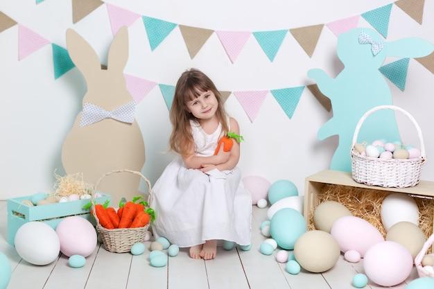 Święta wielkanocne! piękna mała dziewczynka w białej sukni z pisankami i koszem w jasnej scenerii wielkanocnej. lokalizacja wielkanocna, dekoracje. rolnictwo. dziecko i ogród. królik i kolorowe jajka.