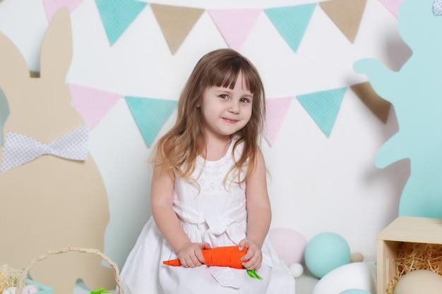 Święta wielkanocne! portret pięknej małej dziewczynki w białej sukni trzyma marchewkę. wielkanocna dekoracja wnętrz, wiosenny wystrój. rodzinne wakacje, tradycje. mały rolnik. żniwny. wegetariańskie, warzywa