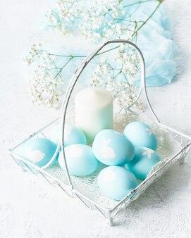 Święta wielkanocne. święto. jasne białe tło, delikatne pastelowe kolory. kwiaty w tle, pionowe