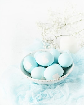 Święta wielkanocne. święto. jasne białe tło, delikatne pastelowe kolory. kwiaty w tle, widok z boku, pionowo