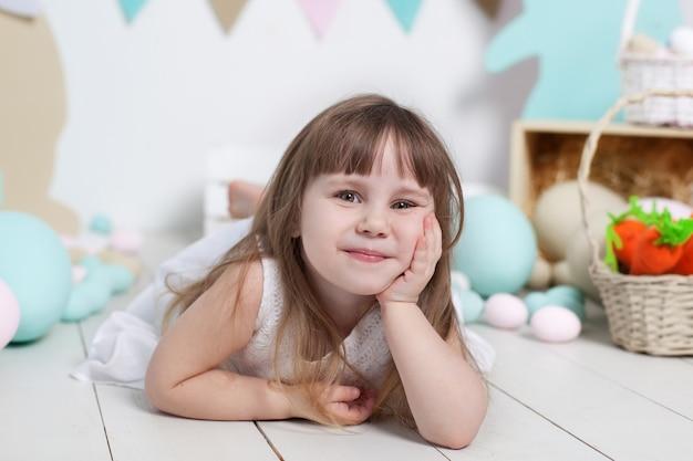 Święta wielkanocne. zakończenie portret pięknej małej dziewczynki twarz. wiele różnych kolorowych pisanek, kolorowe wnętrze wielkanocne. zajączek, marchewka i kolorowe flagi. uśmiechająca się dziewczyna. emocje dziecka.
