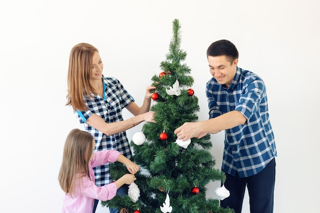 Święta, x-mas i świętowanie koncepcja - szczęśliwa rodzina dekorowanie choinki w wakacje na białym tle.