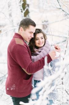 Święta, zima, gorące napoje i ludzie - szczęśliwa para w ciepłych ubraniach, przytulająca się do gałęzi ze śniegiem