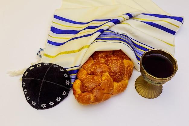Święta żydowskie modlitwa szabatowa szal tallit nakrycie stołu na szabat z zapalonymi świecami, chałką i winem.