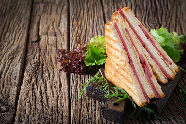 Świetlicowa kanapka - panini z baleronem i serem na drewnianym tle. jedzenie na piknik.