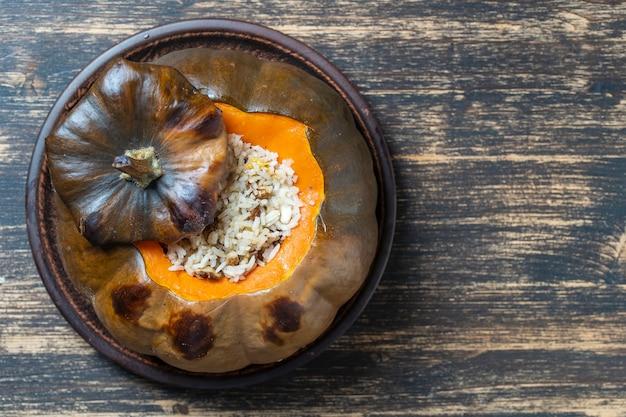 Świetna dynia pieczona z nadzieniem z bliska na talerzu, widok z góry, miejsce na kopię. faszerowana pieczona dynia pomarańczowa, pieczona w całości, wypełniona smaczną mieszanką ryżu, rodzynek i przypraw