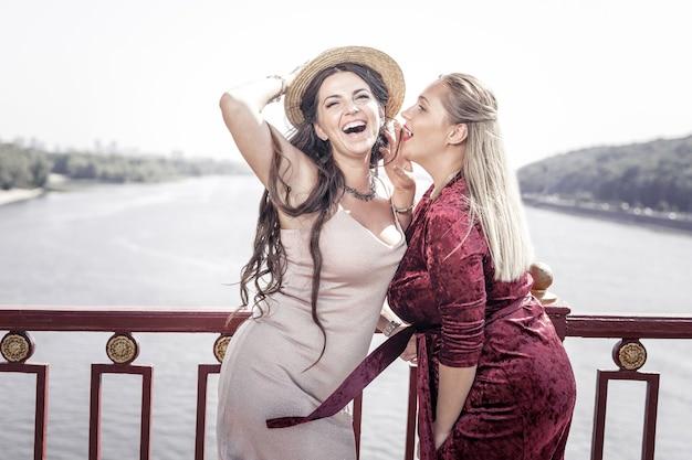 Świetna lokalizacja. pozytywna piękna kobieta stojąca razem z koleżanką na moście, chcąc coś jej powiedzieć