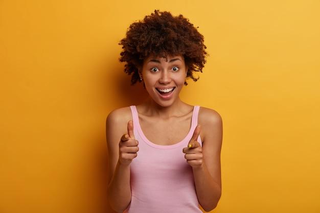 Świetna oferta dla ciebie. radosna kobieta z kręconymi włosami pokazuje znak broni, pozytywnie chichocze, wyraża wybór i wybiera kogoś, nosi zwykłą koszulę, odizolowaną na żółtej ścianie. hej, zapamiętałem cię