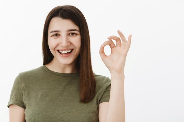 Świetna okazja, potwierdź to. radosna i beztroska optymistyczna europejska brunetka w oliwkowym t-shircie pokazująca dobry znak i uśmiechnięta, zachwycona polecając produkt, nie mająca problemów z doskonałą obsługą