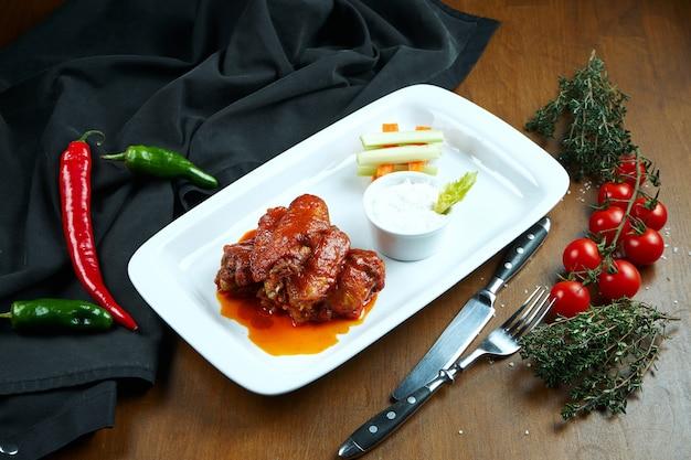 Świetna piwna przekąska - pikantne pieczone bawole skrzydełka. bbq skrzydła z dodatkami sałatki na białym talerzu. ścieśniać. jedzenie w pubie