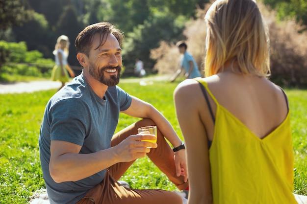 Świetna pogoda. przystojny zainspirowany mężczyzna rozmawia z żoną, podczas gdy ich dzieci bawią się w tle