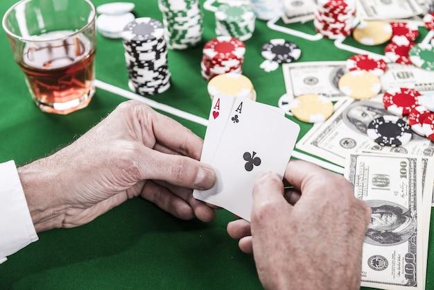 Świetna szansa na wygraną. zbliżenie: mężczyzna trzymający karty siedzący przy stole pokerowym z dużą ilością żetonów i pieniędzy leżących na nim