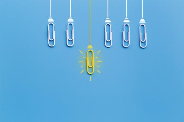 Świetne pomysły z spinaczem, myślenie, kreatywność, żarówka na niebieskim tle, nowe pomysły