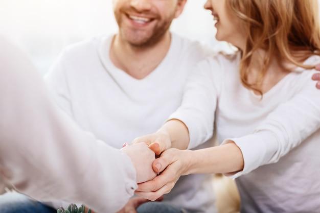 Świetne relacje. zbliżenie na uścisk dłoni psychologa i miłą wesołą atrakcyjną kobietę kończącą sesję psychologiczną