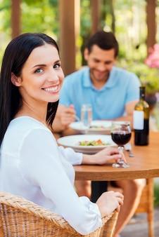 Świetne spędzanie czasu w restauracji. piękna młoda para relaksuje się razem w restauracji na świeżym powietrzu, podczas gdy kobieta patrzy na kamerę i uśmiecha się