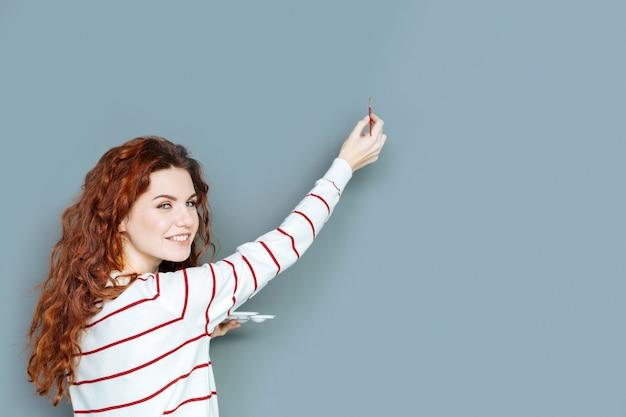 Świetne umiejętności. umiejętnie miła artystka uśmiecha się i zwraca do ciebie podczas malowania na ścianie
