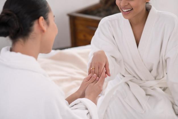 Świetne wydarzenie. przyjemna młoda kobieta trzymając się za ręce przyjaciół, patrząc na jej pierścionek zaręczynowy